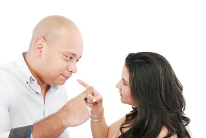 Young couple pointing at each other against a white background