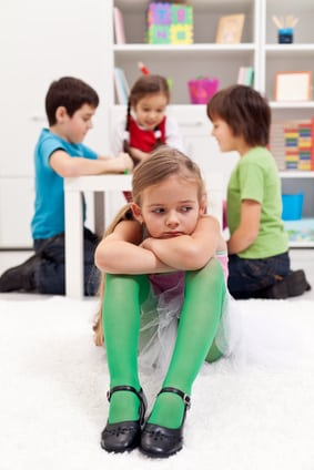 Sad little girl sitting excluded by the other kids