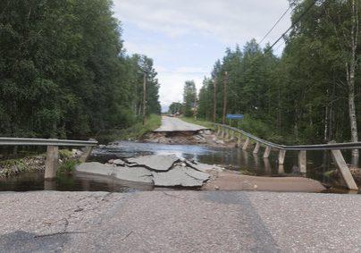 Broken asphalt near a bridge after heavy rain